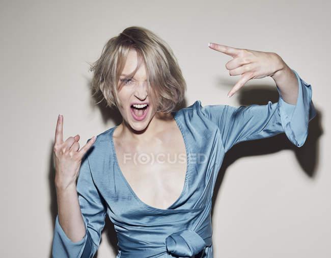 Portrait of blond woman wearing evening dress gesturing — Stock Photo