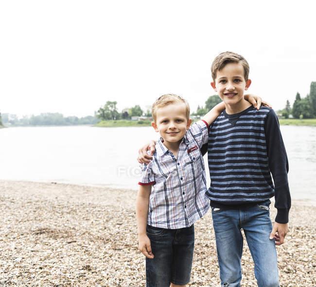 Портрет двух улыбающихся мальчиков, обнимающихся на берегу реки — стоковое фото