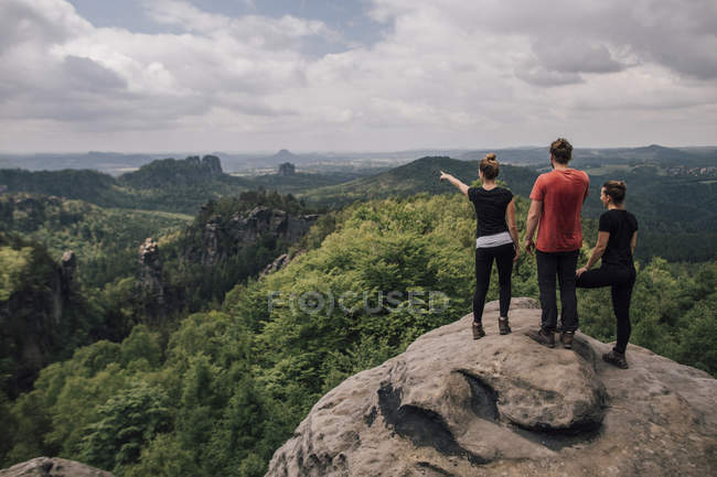 Germany, Saxony, Elbe Sandstone Mountains, friends on a hiking trip standing on rock — Stock Photo
