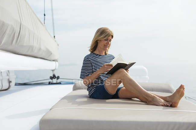 Жінка сидить на палубі Катамаран, читаючи книгу — стокове фото