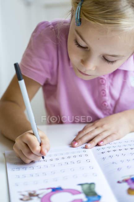 Pequena menina escrevendo números no livro de exercícios — Fotografia de Stock