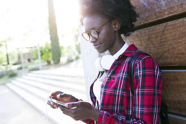 Mujer joven con auriculares mirando el teléfono celular - foto de stock