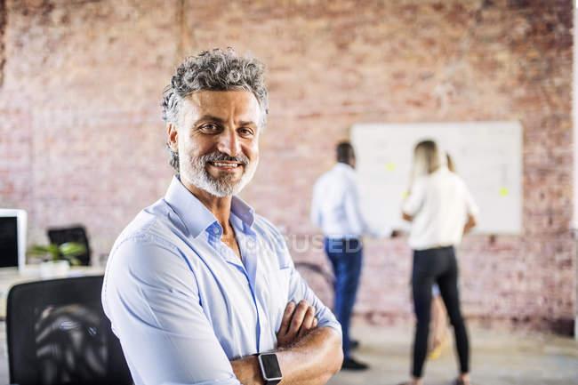 Verticale d'homme d'affaires de sourire dans le bureau avec des collègues à l'arrière-plan — Photo de stock