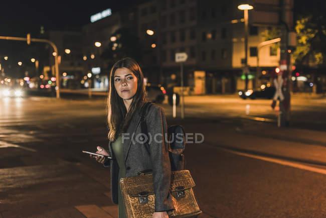 Ritratto di giovane donna d'affari con bagaglio e cellulare di notte — Foto stock