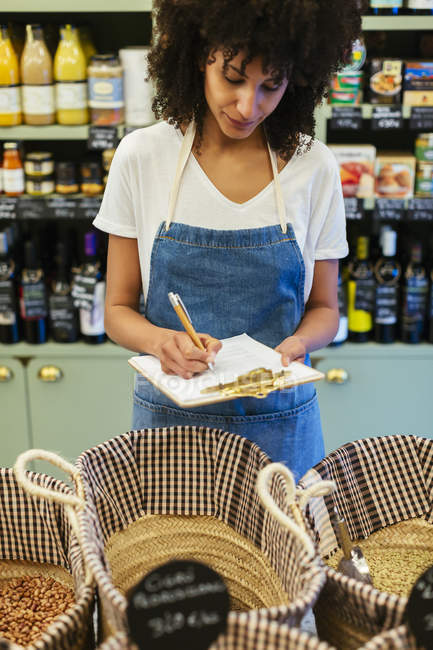 Woman in a store taking notes on clipboard — Stock Photo