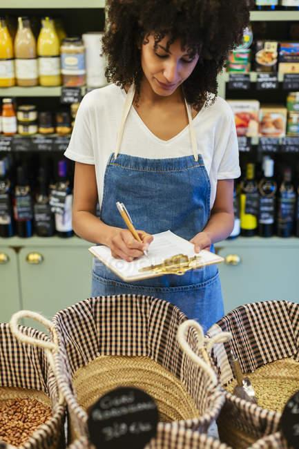 Женщина в магазине делает заметки на планшете — стоковое фото