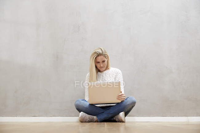 Blond woman sitting on the floor in front of grey wall and using laptop — Stock Photo