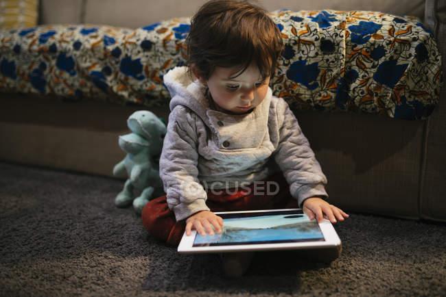 Bebé niña viendo vídeos en una tableta en casa - foto de stock