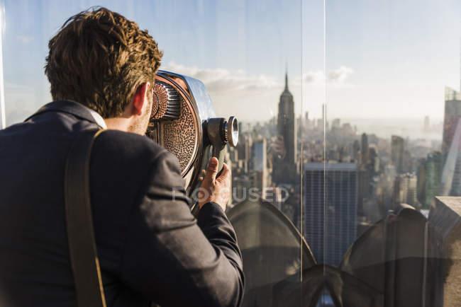 USA, New York, uomo che guarda attraverso un binocolo a monete sul ponte di osservazione del Rockefeller Center — Foto stock