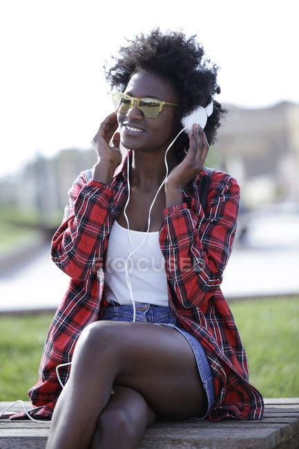 Portrait of smiling young woman sitting on bench listening music with headphones — Stock Photo