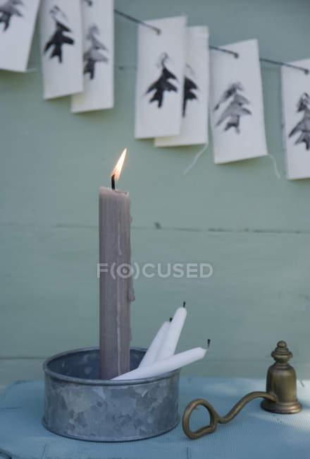 Металічний свічник з палаючою сірою свічкою, гарланд з картопляним друком, латунні свічники. — стокове фото