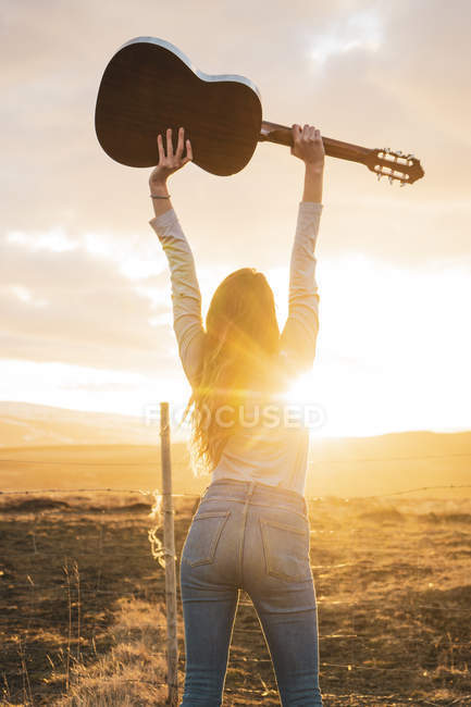 Iceland, woman with guitar at sunset — Stock Photo