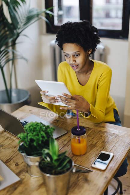 Молода афроамериканська жінка сидить за столом з кількома портативними пристроями. — стокове фото