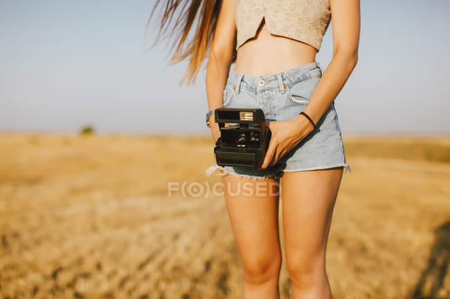 Jovem com câmera instantânea em um campo ao pôr do sol, vista parcial — Fotografia de Stock