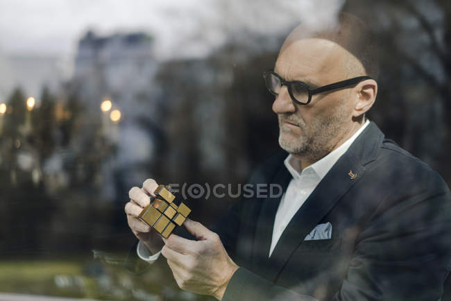 Senior businessman putting together puzzle cube — Stock Photo