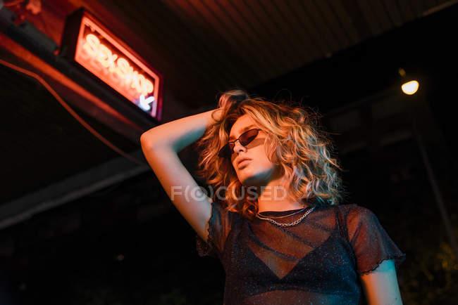 Jeune femme élégante la nuit, debout devant le sex shop — Photo de stock
