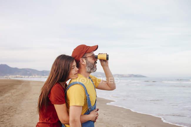 Coppia con binocolo sulla spiaggia — Foto stock