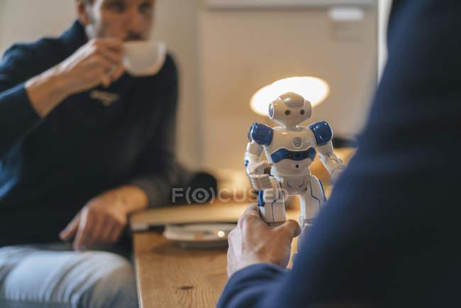Deux hommes et un robot sur la table — Photo de stock
