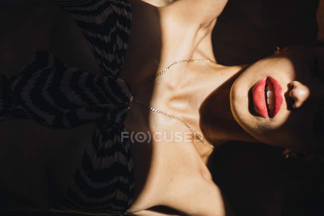 Крупный план губ и шеи красивой молодой женщины в солнечном свете — стоковое фото