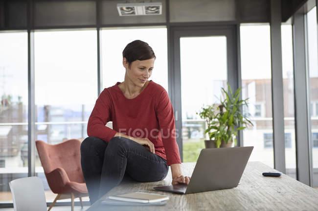 Lächelnde Frau sitzt zu Hause mit Laptop am Tisch — Stockfoto