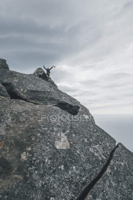 Norway, Lofoten, Moskenesoy, Young man waving from Hermannsdalstinden — Stock Photo