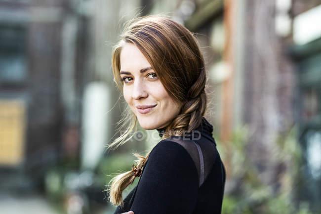 Портрет улыбающейся женщины с косой — стоковое фото