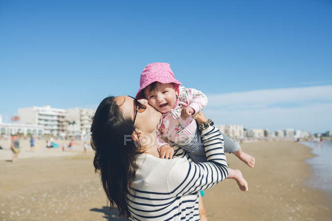 France, La Baule, mother kissing happy baby girl on the beach — Stock Photo