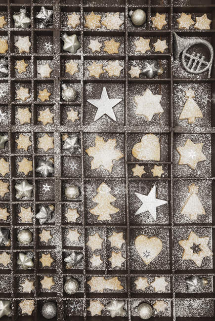 Homemade Christmas cookies, stars and Christmas baubles in old wooden typecase — Stock Photo