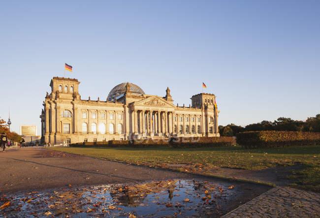 Deutschland, Berlin, Regierungsviertel, Reichstagsgebäude mit Deutschlandfahnen im Herbst, Fernsehturm im Hintergrund — Stockfoto