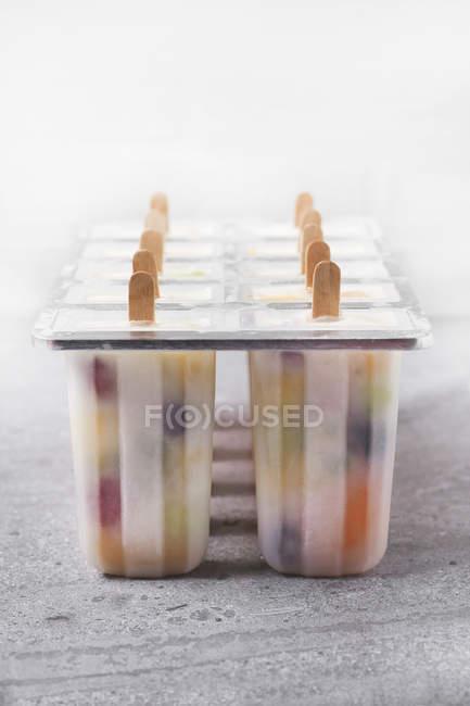 Домашние фрукты и йогурт ледяные леденцы на мраморе — стоковое фото