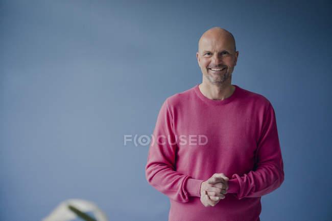 Ritratto di uomo maturo sorridente che indossa un pullover rosa — Foto stock