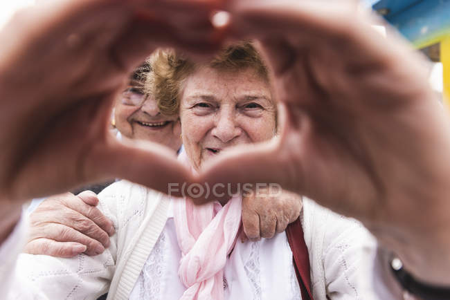 Portrait of happy senior woman shaping heart with her hands — Stock Photo