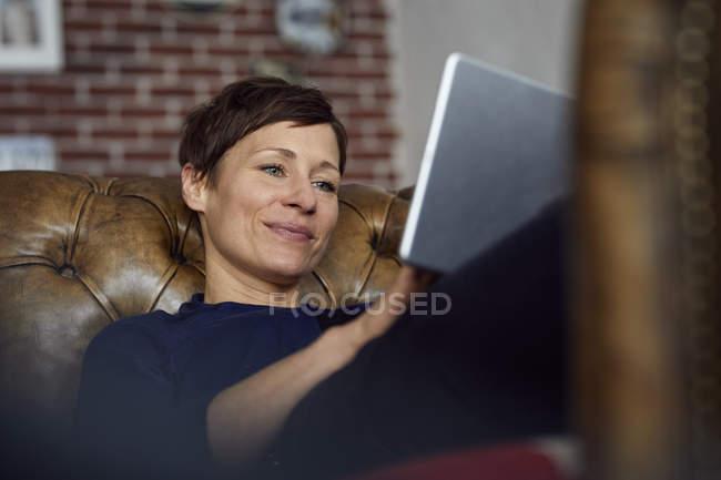 Woamn sitting on sofa at home, using digital tablet — Stock Photo