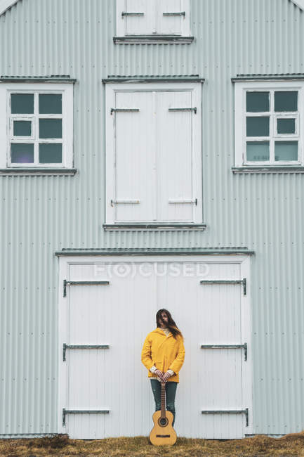 Iceland, woman with guitar standing at house — Stock Photo