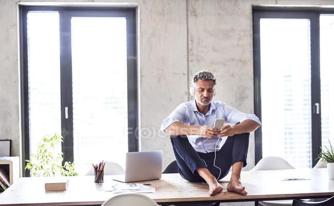 Homme d'affaires mature avec smartphone et écouteurs assis pieds nus sur le bureau au bureau — Photo de stock