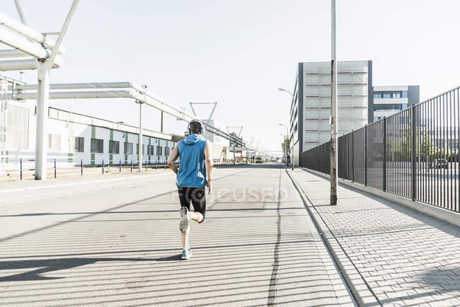 Joven atleta trotando en la ciudad - foto de stock