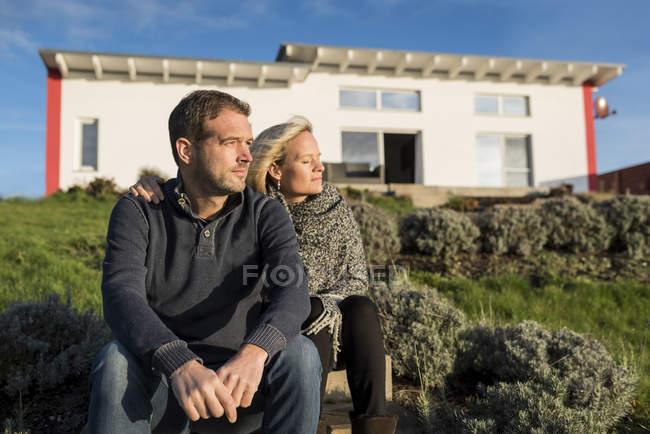 Coppia seduta al sole, davanti alla loro casa — Foto stock