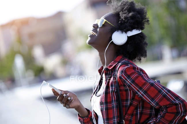 Portrait of laughing young woman using headphones and cell phone — Stock Photo