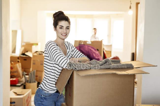 Молодая женщина переезжает, распаковывает картонные коробки — стоковое фото