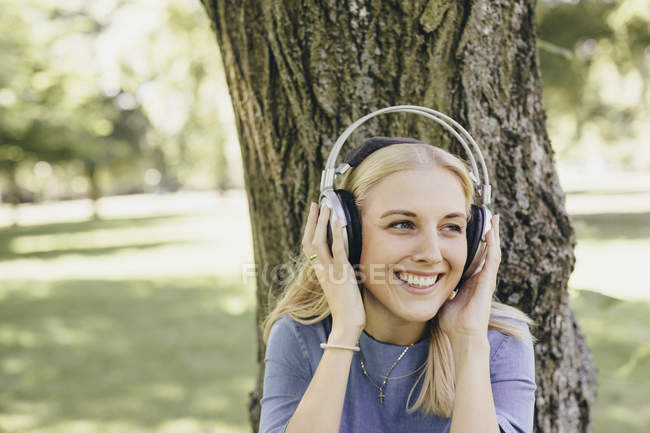 Happy young woman at tree trunk in a park wearing headphones — Stock Photo