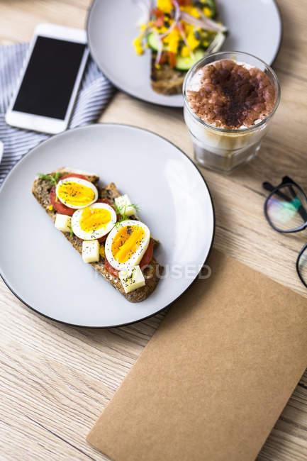 Вегетаріанський сніданок з хлібом, яйцями і томатними скибочками на тарілку, латте Macchiato, смартфон, ноутбук — стокове фото