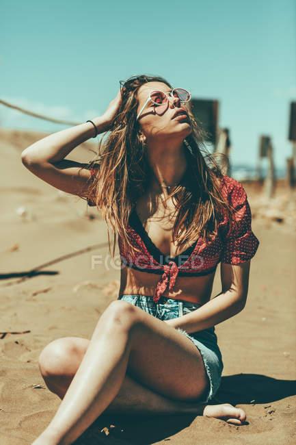 Молодая женщина сидит на песчаном пляже — стоковое фото