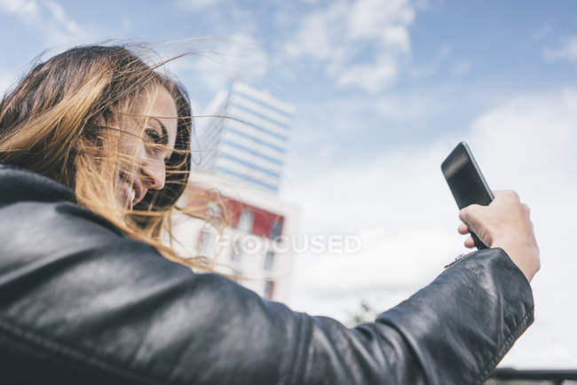 Smiling young woman taking a selfie outdoors — Stock Photo