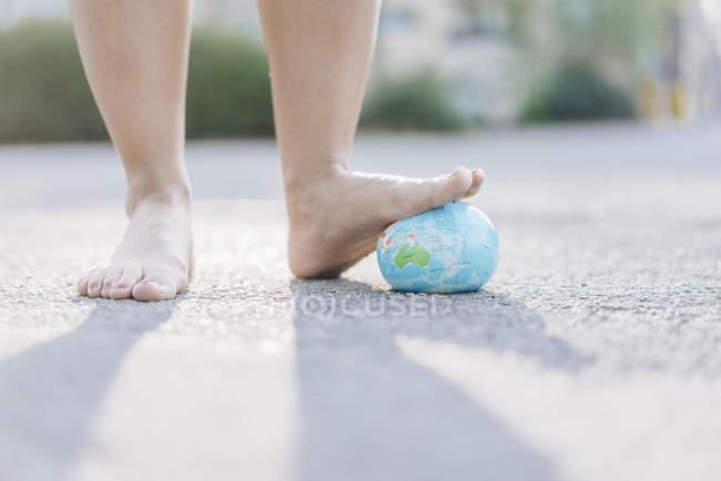 Pé de jovem mulher pisando no globo — Fotografia de Stock