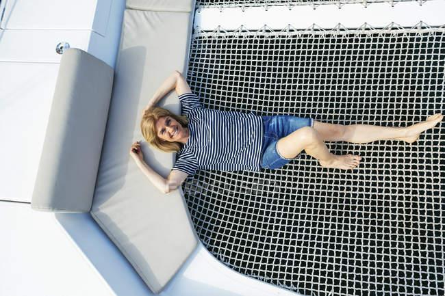 Mulher madura que relaxa no Trampoline do catamarã — Fotografia de Stock
