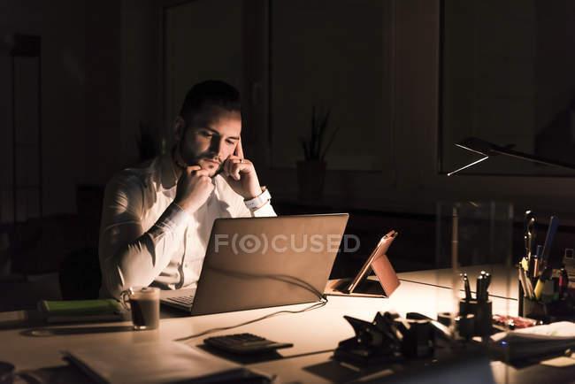 Homme d'affaires pensif travaillant sur ordinateur portable dans le bureau la nuit — Photo de stock