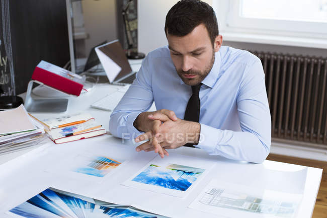 Businessman at desk in office looking at printouts — Stock Photo
