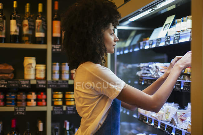 Woman working at shelf in a store — Stock Photo