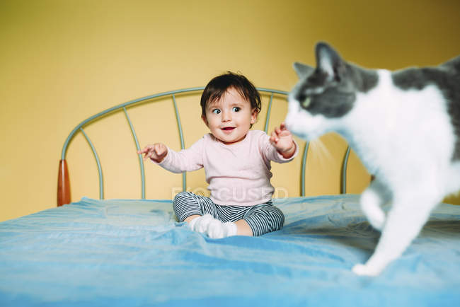 Surprised baby girl with cat on the bed — Stock Photo