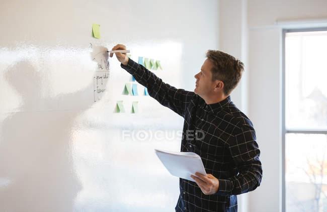 Homme d'affaires au bureau écrivant sur tableau blanc — Photo de stock